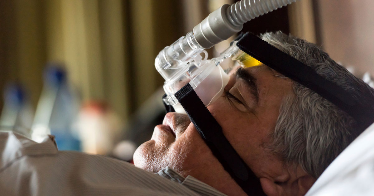 Man with sleep apnea oxygen mask on while he sleeps