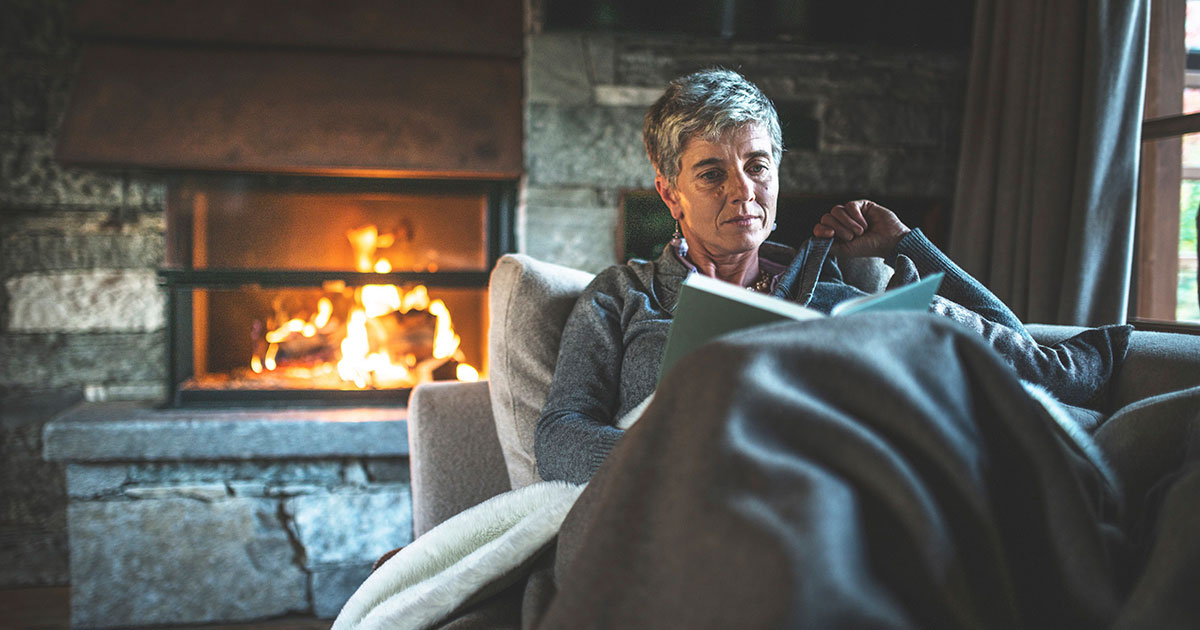 Woman reading on the couch by the fireplace