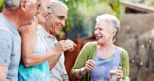 Older people outside, blowing bubbles