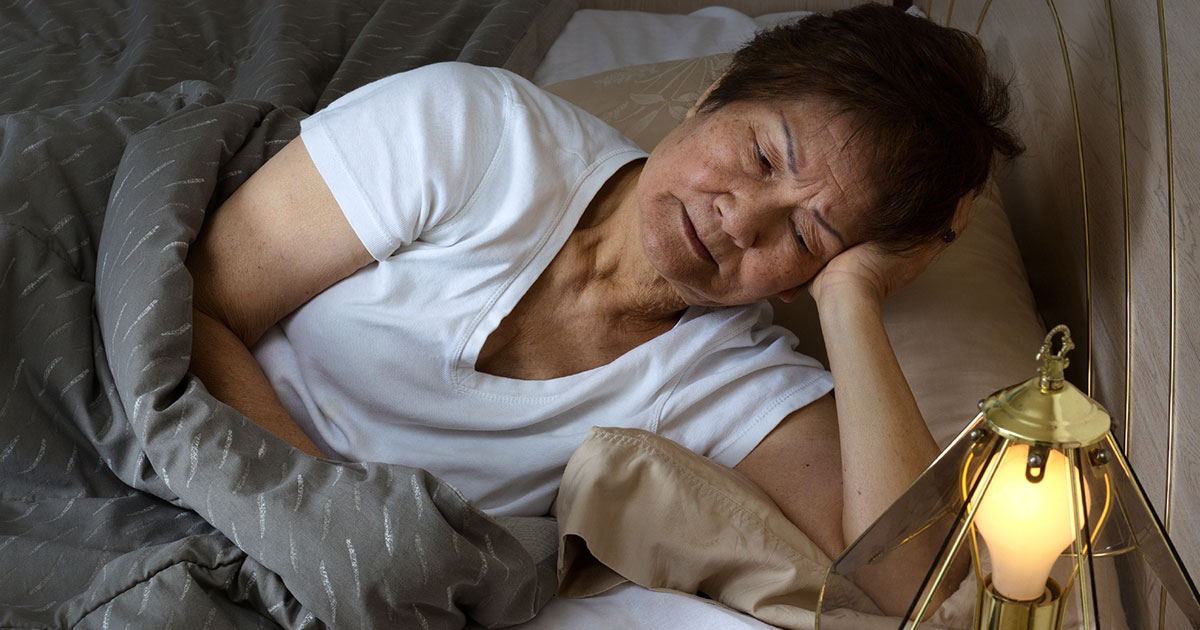 Woman looking uncomfortable lying in bed