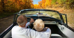 Man and woman driving in convertible on a fall day