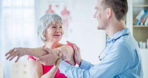 Physical therapist helping a woman stretch her arm