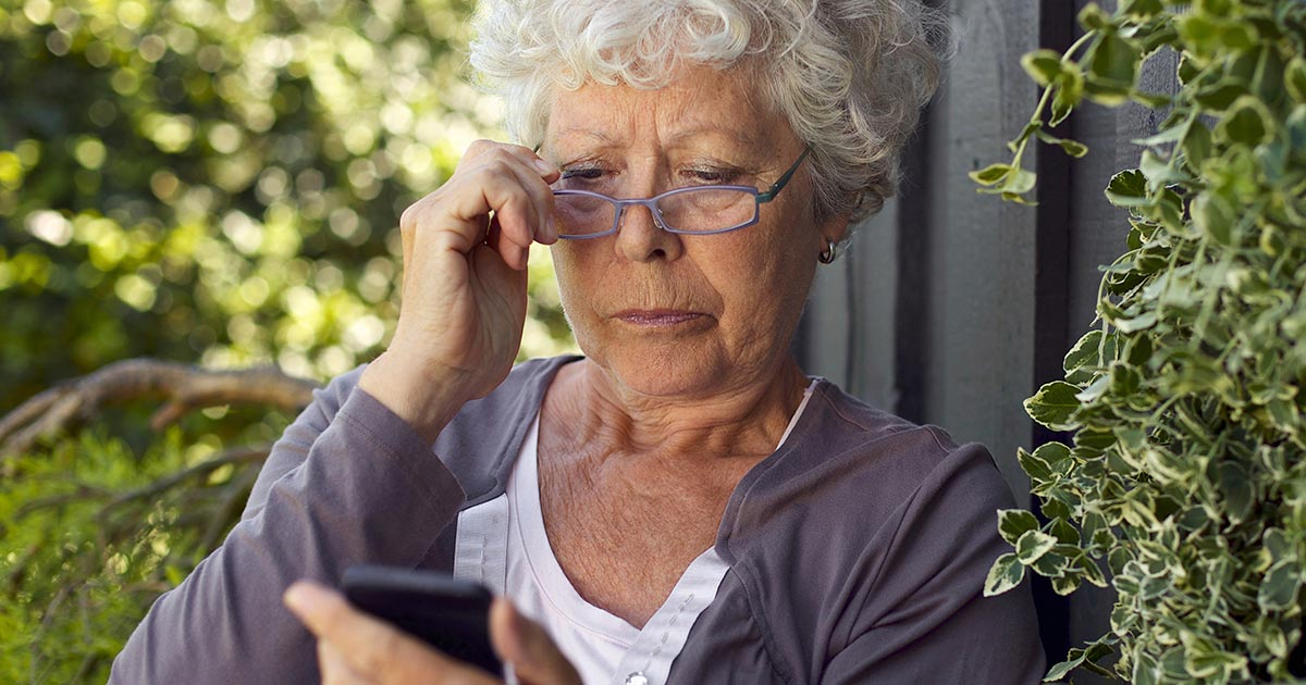 Older woman looking at a phone outside