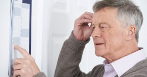 Older man looking at a calendar and looking confused