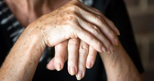 Older woman clasping hands