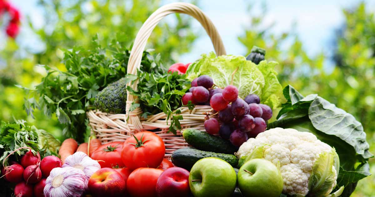 Basket of vegetables with other vegetables and fruits in front