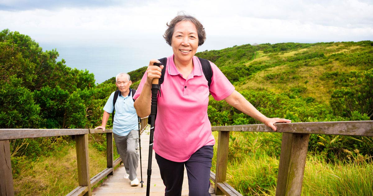 Older man and woman hiking up wooden stairs