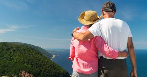 Man and woman with arms around each other standing at top of Skyline Trail in Cape Breton