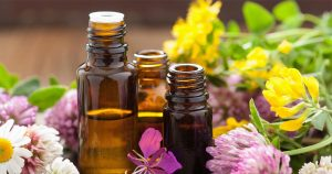 Vials of essential oils with flowers in background