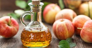 Bottle of apple cider vinegar with apples in background