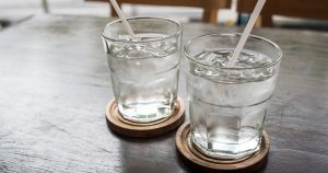 Two glasses of water with straws in them